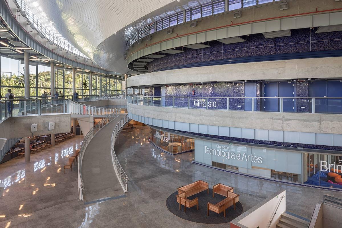 Foto da parte interna do Sesc Jundiaí, com sua arquitetura moderna, com rampas, espaços coletivos e vidraças.