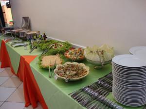 Mesa com buffet de pratos quentes e saladas